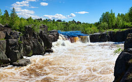 Water cascade between the grey rocks. In summer season. Blue sky with clouds. Pines on the stones. Karelia, Russia Stock Photo