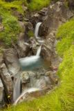 Water cascade in a small rocky gorge Stock Photo