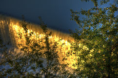 Water cascade on the Vltava river in Prague during early morning sun with vegetation in the foreground Stock Image