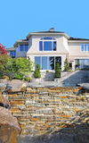 Beautiful Home Exterior with Manmade Waterfall. Water cascades over a manmade waterfall with the gorgeous new home as the backdrop stock photo