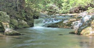 Rich Mountain Creek in Stone Mountain State Park. Water cascades over mossy rocks in Rich Mountain Creek.  Stone Mountain State Park in Low Gap, North Carolina Royalty Free Stock Photos