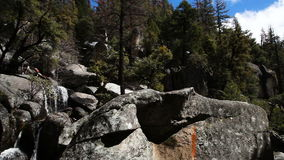 Water Cascading Down Granite Rock Landscape Yosemite Park California. Granite Rocks And Trees With Water Cascading Down Blue Sky White Clouds stock video footage