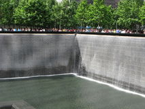 Water cascading down the side of the fountain at One World Trade Center. One World Trade Center memorial fountain on a clear day with sunshine Royalty Free Stock Images
