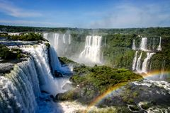 Water cascading over the Iguacu falls with rainbow in foreground. In Brazil royalty free stock photo