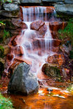 Water Cascading Over Red Algae Covered Rocks stock photo