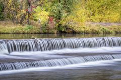 Water cascading over a river diversion dam. Water cascading over a diversion dam on the Poudre River with fall colors in bakcground royalty free stock image