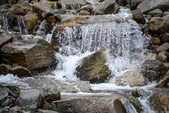 Water cascading over rocks. In the mountains Stock Images