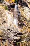 Water cascading over rocks, waterfall and autumn colors in the mountains, yellow and red trees Stock Images