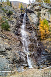 Water cascading over rocks, waterfall and autumn colors in the mountains, yellow and red trees Royalty Free Stock Photos