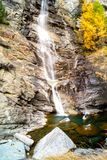 Water cascading over rocks, waterfall and autumn colors in the mountains, yellow and red trees Royalty Free Stock Image