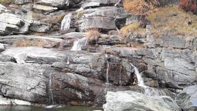 Water cascading over rocks, waterfall and autumn colors in the mountains, yellow and red trees. Waterfall and autumn colors water cascading over rocks stock footage