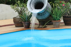 Water cascading from an urn in pool Stock Images