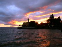 Water castle under burning sky. Churned lake at the Castle, royal building on the lakeshore, Landscape on the lake after the storm, Water castle in southern Stock Image