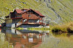 Lake cabin mirrored in water in Carpathians  Royalty Free Stock Image