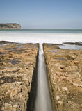 Water Channel in the Beach. Seascape with a channel in the center of the image bearing seawater through the rocks to the breaking waves on the shore Royalty Free Stock Photo
