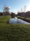 Water channel hugt by green grass stock photography