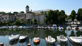 The water channel with parked motor boats and Catholic church. Rimini, Italy stock video
