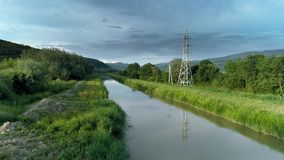 Water channel is a tributary of a river with power lines across. stock video