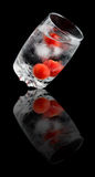 Water with Cherry tomatoes and ice  in a glass cup Stock Images