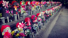 Water children in buddhist temple in Tokyo. Jizo stone statues standing in long rows, some wearing bibs or knitted caps and festooned with cute charms. The royalty free stock images
