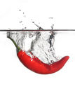 Water chili. Red hot chili splashing into water on isolated white background Stock Photo