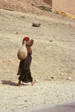 Water chore. A woman bare feet in traditionnal dressing is carrying a clay water pitcher on shoulder in southern Morocco stock photography