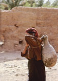 Water chore. A woman in traditionnal dressing is carrying a clay water pitcher on shoulder in southern Morocco stock photo