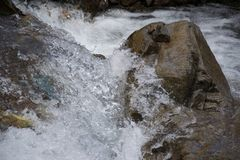 Water churns around a rock in a river royalty free stock photo