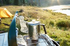 Water or coffee boiling in a stainless steel pot. On the burner of a camping gas stove overlooking a mountain lake and wilderness Stock Photography