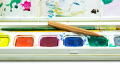 Water color box, brushes and pencil on white background Stock Image