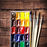 Water color drawing, paints and brushes over vintage wooden back Stock Photos