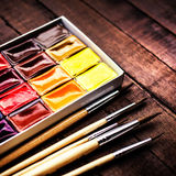 Water color drawing, paints and brushes over vintage wooden back Royalty Free Stock Photos