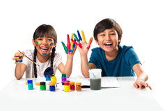 Water Color. Two smiling little kids at the table draw with water color, Isolated over white Royalty Free Stock Photo