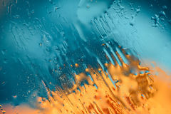 Water colored drops painting. Water texture painting on illuminated glass Royalty Free Stock Photo