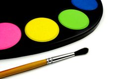 Water colors on black palette and paintbrush Stock Photos