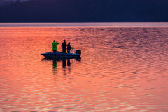 Bass Fishing Boat Dam Light Reflections. Dawn morning color water light reflections with bass fishermen in boat royalty free stock photo