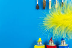 Water colors and paint brush. Water colors, paint brushes and feathers on blue background Stock Photos