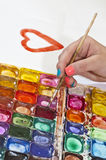 Water colour paints and brush for drawing by paints in hands of Stock Photo