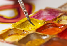 Water colour paints and brush for drawing by paints in hands of Stock Photography