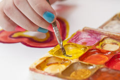 Water colour paints and brush for drawing by paints in hands of Royalty Free Stock Photos