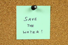 Water conservation. Green sticky note pinned to an office notice board. Save the water - environmental conservation and water saving info stock photography