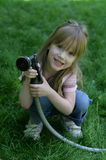 Water conservation. A child holding a water hose Stock Images