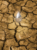 Water conservation. Water drop falling on parched, cracked ground.  Concept for importance of water resources, breaking the drought Stock Image