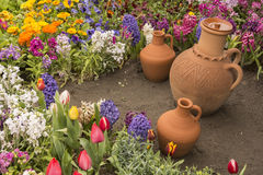 Water Container Earthenware Jugs Inside Flower Bed Stock Photography