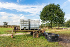 Water containers on cart for cattle in meadow. Water containers on trailer for cows in pasture Royalty Free Stock Photography