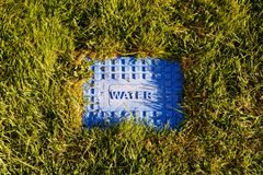 Metal ridged cover with WATER on it seated in grass. stock photo