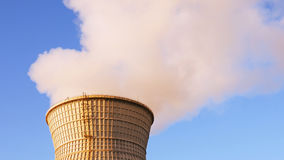 Water cooling tower stack smoke over blue sky. Background. Energy generation and air environment pollution industrial scene Royalty Free Stock Images
