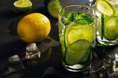 Water with cucumber, lemon and mint, detox. Refreshing drink in backlight. royalty free stock photography