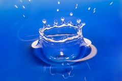 Water cup. Water bowl formed at falling a drop. The tinted water stock photography