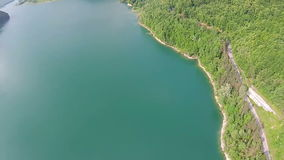 Water dam aerial panning. Aerial panning  above an artificial water dam in the mountains , revealing the arched concrete wall construction and the accumulation stock footage